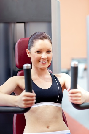 Beautiful athletic woman using a bench press smiling at the camera Stock Photo - 10129878