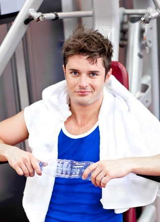 musculation: Handsome man sitting on a bench press  after exercises