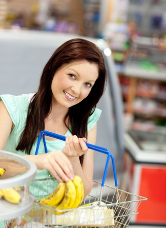 Cute woman putting bananas in her shopping-basket in a grocery store Stock Photo - 10133838