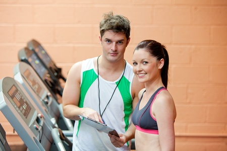 musculation: Pretty woman on a treadmill with her coach showing results