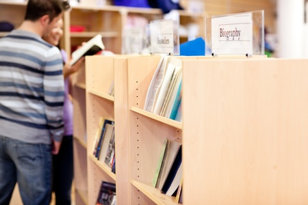 Close-up of a bookshelves in a library with students reading book photo