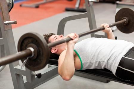 levantando pesas: Joven musculoso con el levantamiento de pesas acostado en un centro de fitness