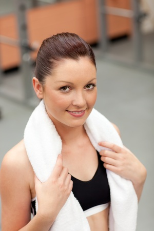 musculation: Attractive athletic woman with towel around the neck smiling at the camera Stock Photo