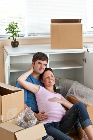 Adorable couple sitting on the floor in their new house during removal photo