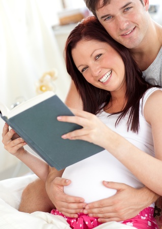 Cheerful future parents reading a book sitting on their bed during the morning photo