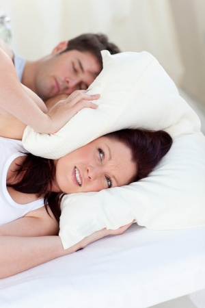 snoring: Stressed future mom with head under the pillow in bed with her husband snoring