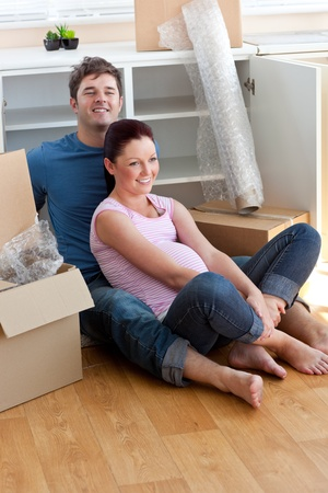 Joyful young future parents sitting on the floor surrounded by cardboards photo