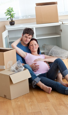 Future parents relaxing on the floor during a break after unpacking boxes photo