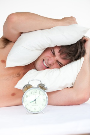 woken: Angry man woken up by his alarm clock putting pillow on his head