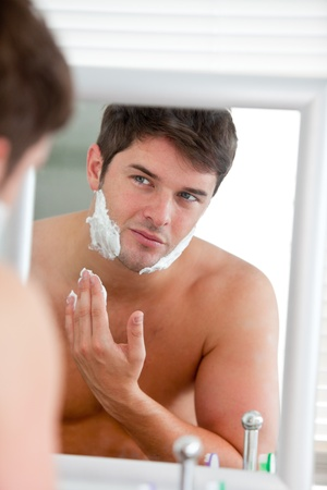 Young man putting some shaving foam looking his face in the mirror photo