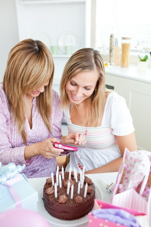 Two bright female friends looking at pictures during a birthday party in the kitchen photo