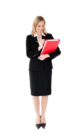 Radiant businesswoman writing on a paper against white background photo