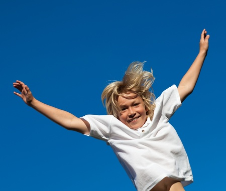 Smiling Kid Jumping in the air outdoor  photo