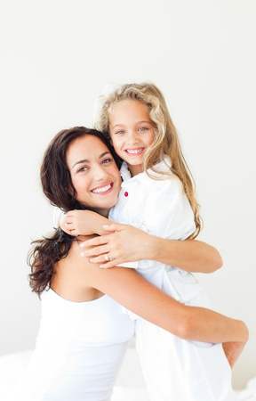 delighted: Delighted mother and daughter on a white bed