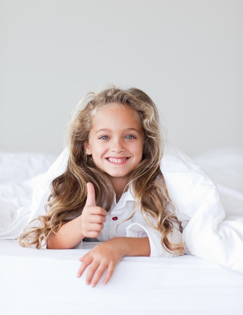 Smiling girl with thumbs up  photo