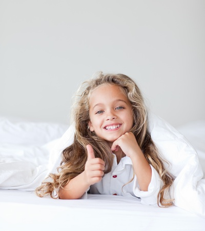 engel: Little cute girl lying on her white bed Stock Photo