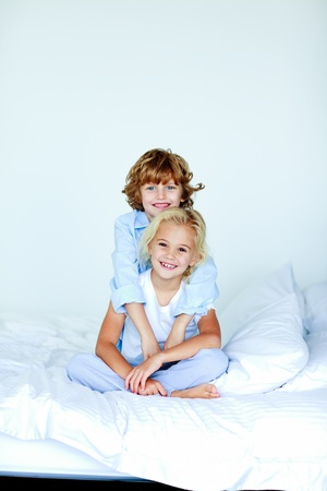Sister and brother embracing in bed  photo