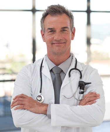 Elderly doctor with folded arms smiling at the camera Stock Photo - 10162290