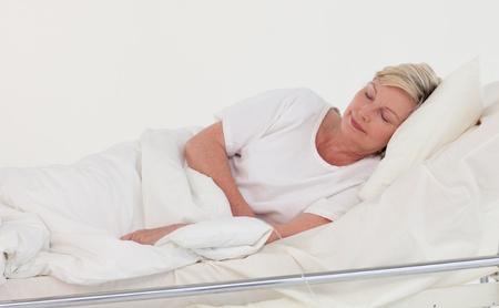 Oudere patiënt liggend in bed Stockfoto