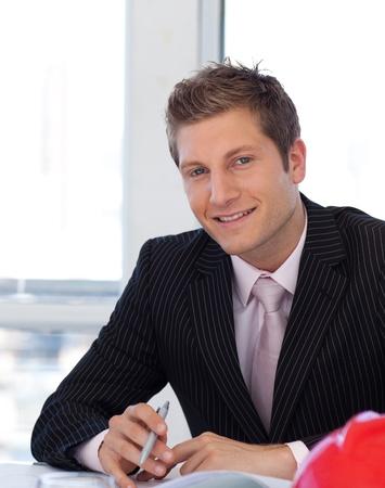 Joyful businessman working at his desk  photo