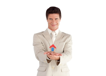 Portrait of a smiling young businessman presenting a sample of house  photo