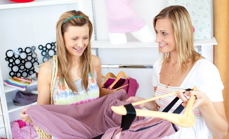 choosing clothes: Two cheerful women choosing clothes together