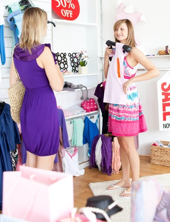 trying: Two radiant women choosing clothes together Stock Photo