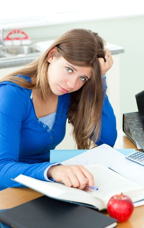 Frustated woman with books sitting at a desk Stock Photo - 10175835