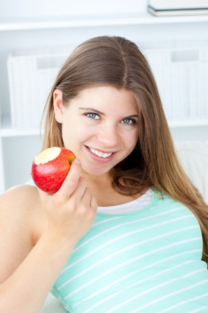 Positive woman eating an apple smiling at the camera Stock Photo - 10175747