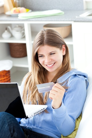 Happy woman with a credit card and a laptop photo