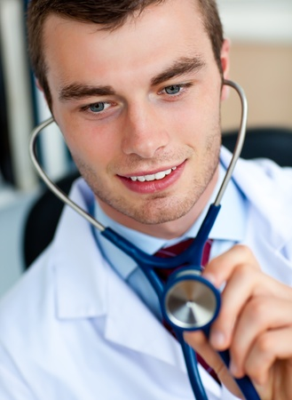 Charming young doctor examining with a stethoscope  photo