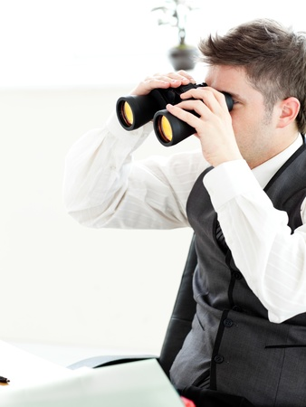 Close-up of a young businessman looking through binoculars isolated photo