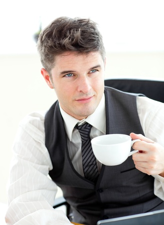 man drinking coffee: Confident young businessman with a laptop holding a coffee
