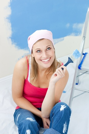 Cheerful woman  painting a room  photo