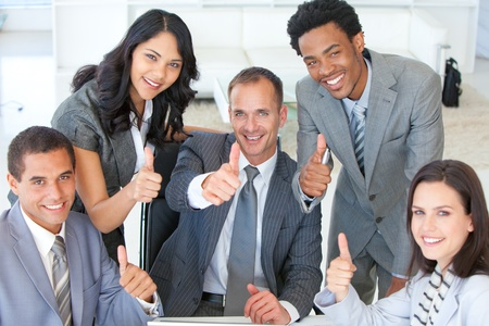 male's thumb: Business team with thumbs up in office Stock Photo