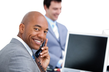 answering phone: Happy businessman on phone and his colleague working at a comput