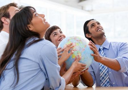 negocios internacionales: Equipo internacional de negocios la celebraci�n de un globo terr�queo Foto de archivo