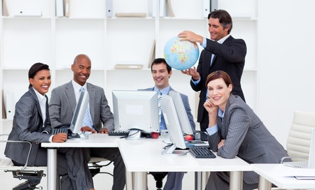 teaming: Smiling manager holding a globe with his team working at computers