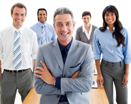 manager office: Smiling manager with folded arms in front of his team