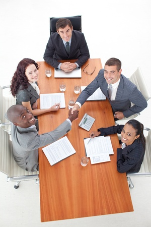 agreement: Smiling multi-ethnic business team shaking hand