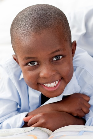 african student: Giovane ragazzo disteso sul suo letto sorridente Archivio Fotografico
