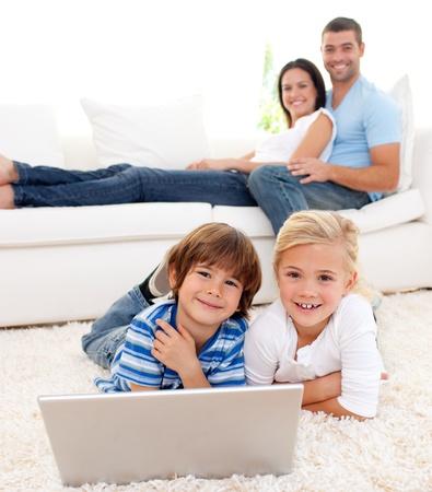 Amar a la familia usando un ordenador portátil en la sala de estar Foto de archivo