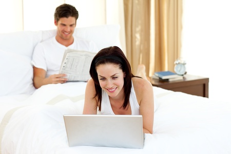 Woman using laptop on her bed photo