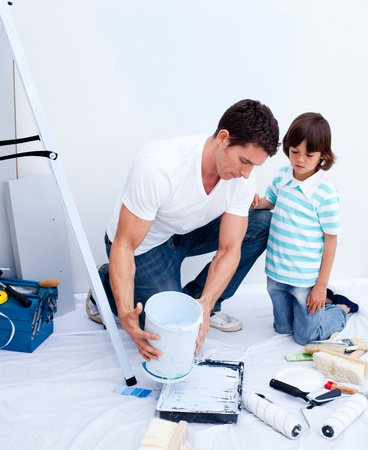 Attentive father and his son decorating their house photo