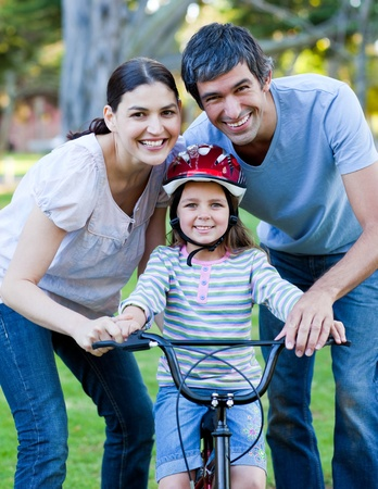 recreational area: Happy family looking at the camera while riding a bike