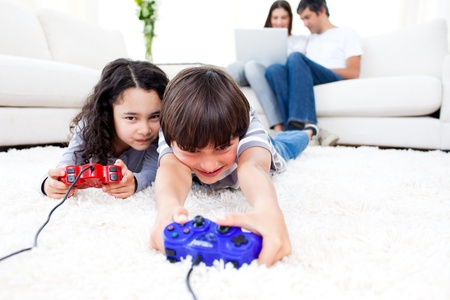 game room: Excited children playing video games lying on the floor