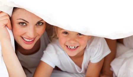 Gl�ckliche Mutter und ihr blondes M�dchen spielen zusammen auf einem Bett  Lizenzfreie Bilder