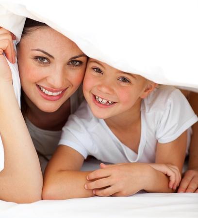 Fr�hlich Mutter und ihr kleines M�dchen spielen zusammen auf einem Bett  Lizenzfreie Bilder