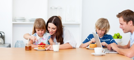 Happy family eating breakfast in the kitchen photo