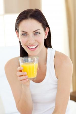 drinking juice: Smiling woman drinking orange juice